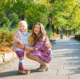 Full length portrait of happy mother and daughter at the park.
