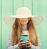 Cute little girl stands near a turquoise wall in white hat and holding cup.