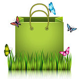 Green paper shopping bag on the meadow grass.