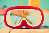sand, dive mask and starfish
