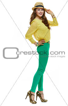 Smiling brunette woman in hat looking aside on white background
