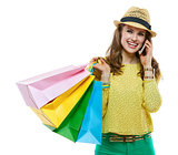 Smiling woman in hat with shopping bags talking cellphone