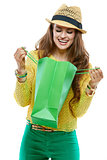 Smiling woman in hat looking inside of the green shopping bags