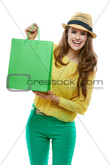 Portrait of smiling woman in hat showing green shopping bags