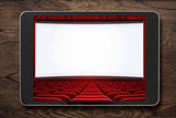 Tablet pc on wooden table with cinema screen displayed.