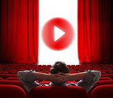 online cinema screen with open red curtain and play media button in center