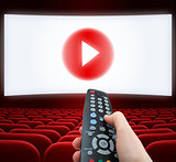 cinema screen with play media button in center and remote control in hand