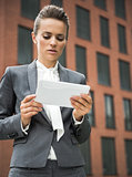 Modern business woman against office building using tablet PC