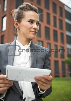 Business woman with tablet PC near office building looking aside