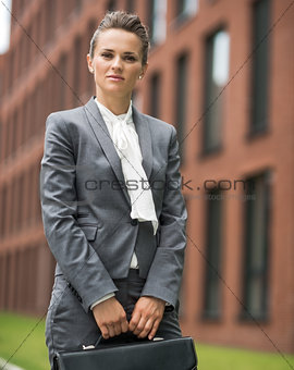 Portrait of business woman with briefcase near office building