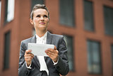 Modern business woman with tablet PC against office building