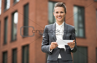 Smiling business woman using tablet PC against office building