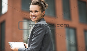 Smiling business woman against office building using tablet PC