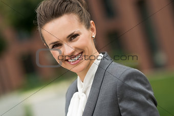 Portrait of smiling modern business woman near office building