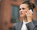 Modern business woman against office building talking smartphone