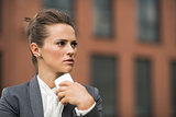 Pensive business woman near office building talking smartphone
