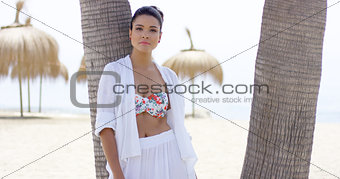 Serious single woman leaning against palm tree
