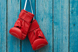 Pair of boxing gloves hanging in a rustic wooden wall