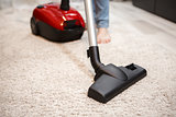 Maid cleaning carpet with modern red vacuum cleaner