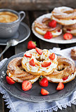 Cream puff rings decorated with fresh strawberry and caramel sau
