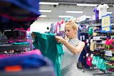 Woman shopping sportswear in sports store.