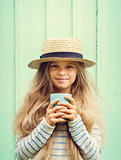 Cute little girl stands near a turquoise wall in boater hat and holding cup. Space for text