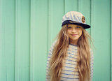Cute little girl stands near a turquoise wall in sailor hat and smiling Space for text.