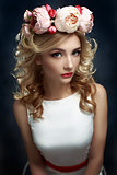Young beautiful woman with bright flowers on her head