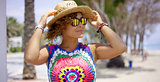 Pretty woman in sunglasses adjusting hat