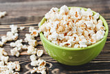 Sweet Caramel Popcorn in Green Bowl on Wooden Background