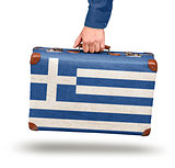 Male hand holding vintage Greek flag suitcase