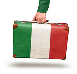 Male hand holding vintage Italian flag suitcase