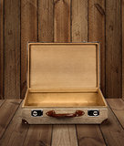 Empty vintage suitcase wooden plank background