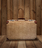 Vintage suitcase on wooden plank background