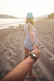 Girl holding a hand man on the beach
