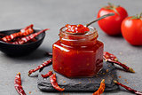 Tomato and chili sauce, jam, confiture in a glass jar on a grey stone background