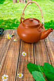 Brown teapoton on wooden with mint and chamomile table in garden and on nature background. Tea concept. Closeup.