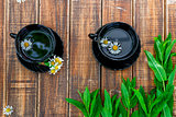 Two black cup of tea with chamomile near fresh mint on wooden table background. Tea concept. Frame, copy space. Top view.