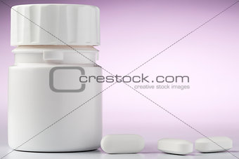 Bottle of aspirin drugs and three pills in the foreground
