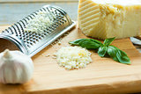 Heap of grated Parmesan on wooden background with leaf of basili