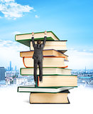 Businessman hanging on top of stack books