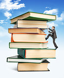 Pile of books with businessman climbing it