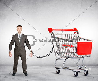 Businessman chained to shopping cart