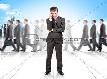 Thinking businessman. Many people on background