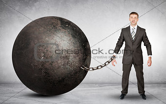 Businessman chained to large ball