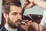 The hands of young barber making haircut attractive man in barbershop