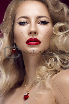 Beautiful blonde in a Hollywood manner with curls, red lips. Beauty face.