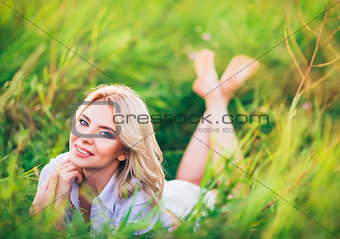 Positive attractive young woman lying among green grass