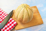Cantaloupe melon and knife on rustic wooden table