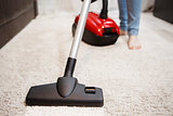Woman doing cleaning in room, vacuuming white carpet